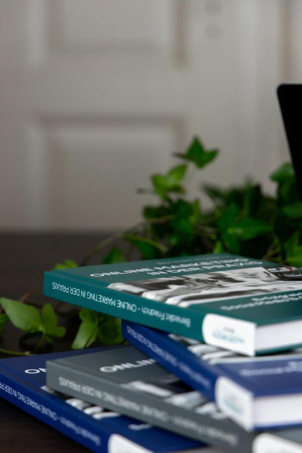 Bücherstapel im Vordergrund, Pflanze im Hintergrund
